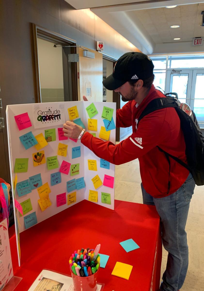 A Student filling out a Gratitiude Graffiti Tri-Fold