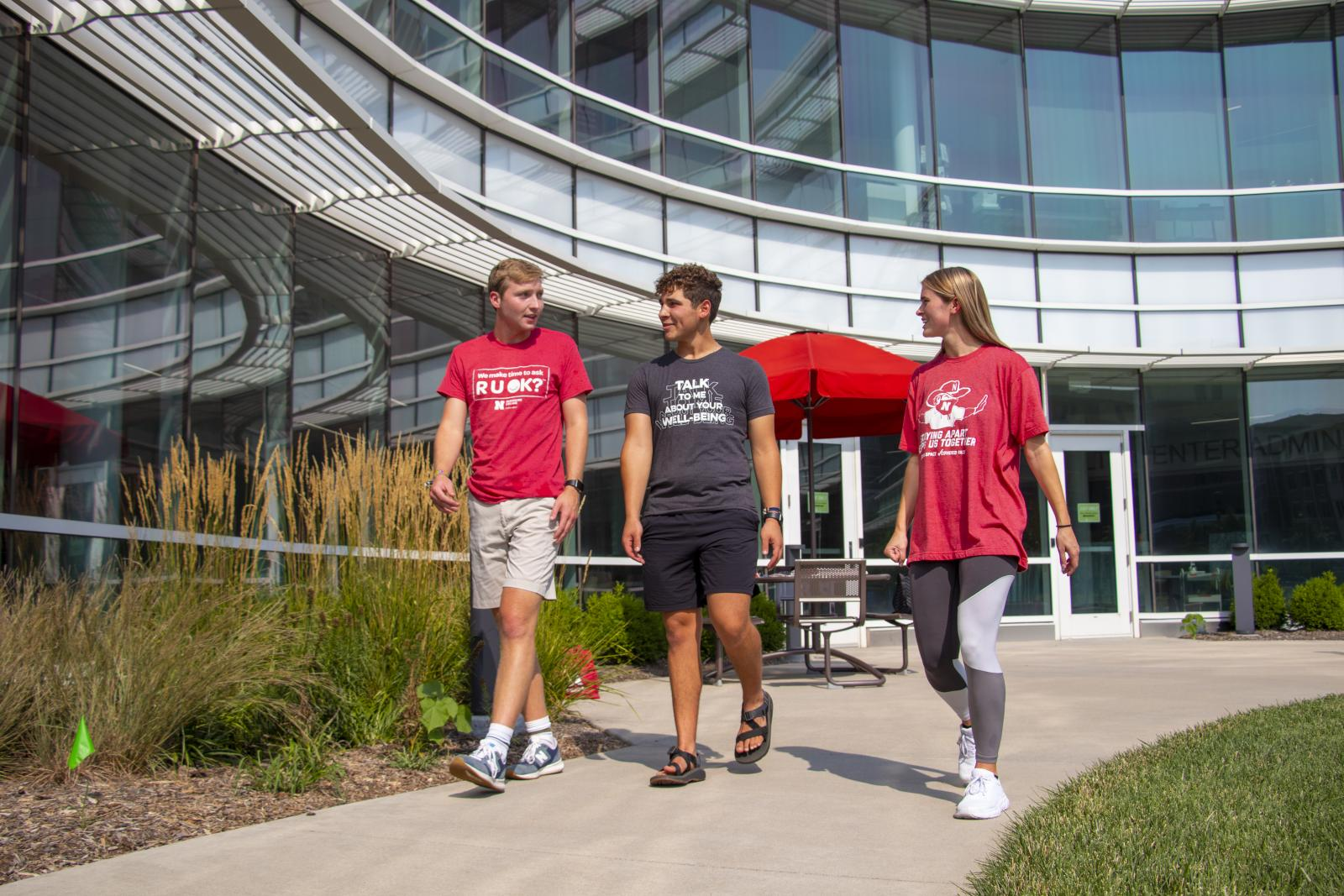 Well-being coaches walk in front of UHC building