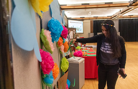 Woman looking at paper flowers at Fresh Check Day