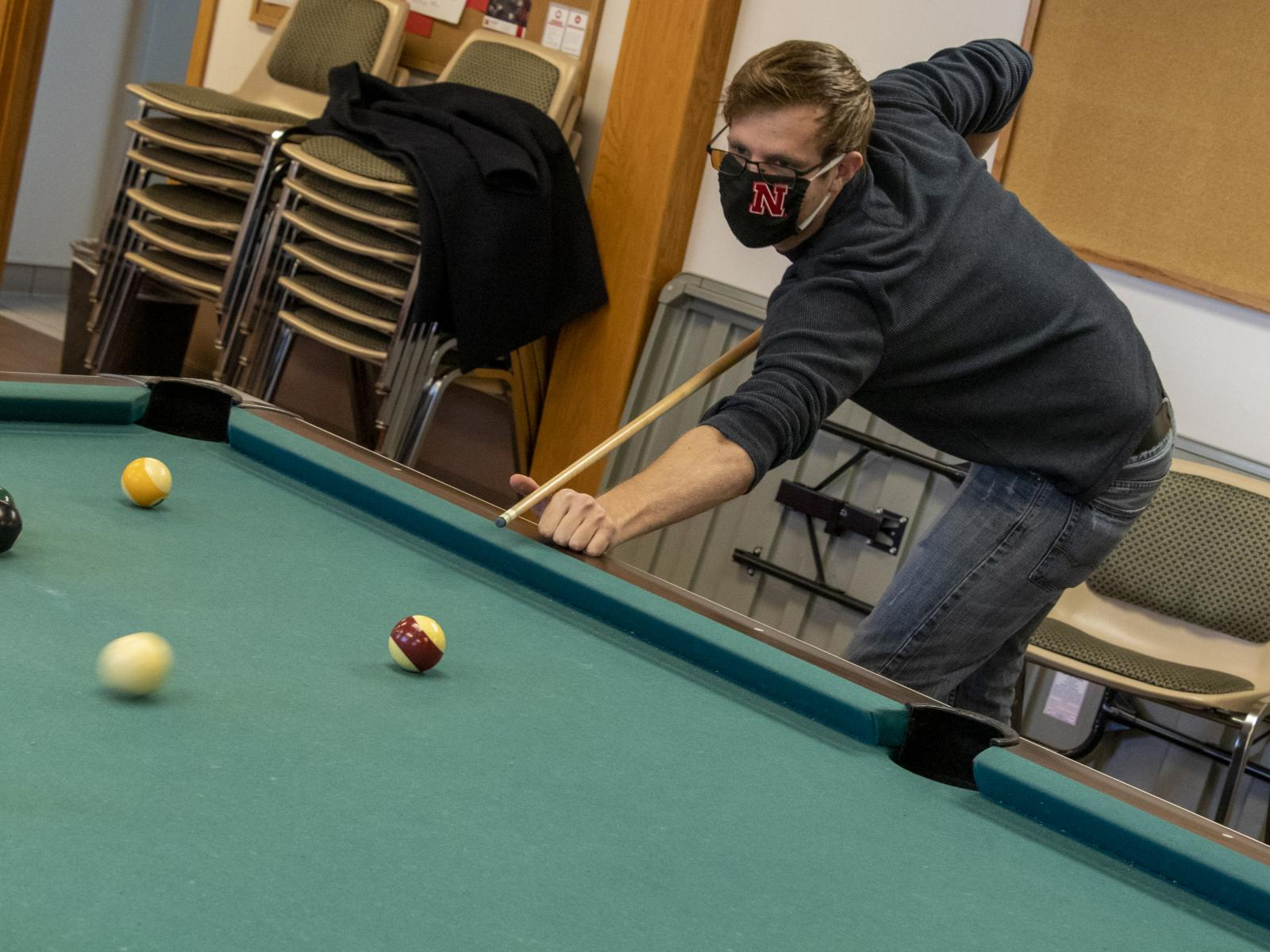Student plays pool in Husker Hall