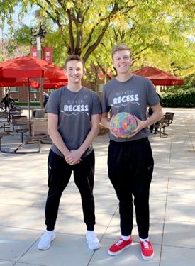 Men posing with a ball at recess