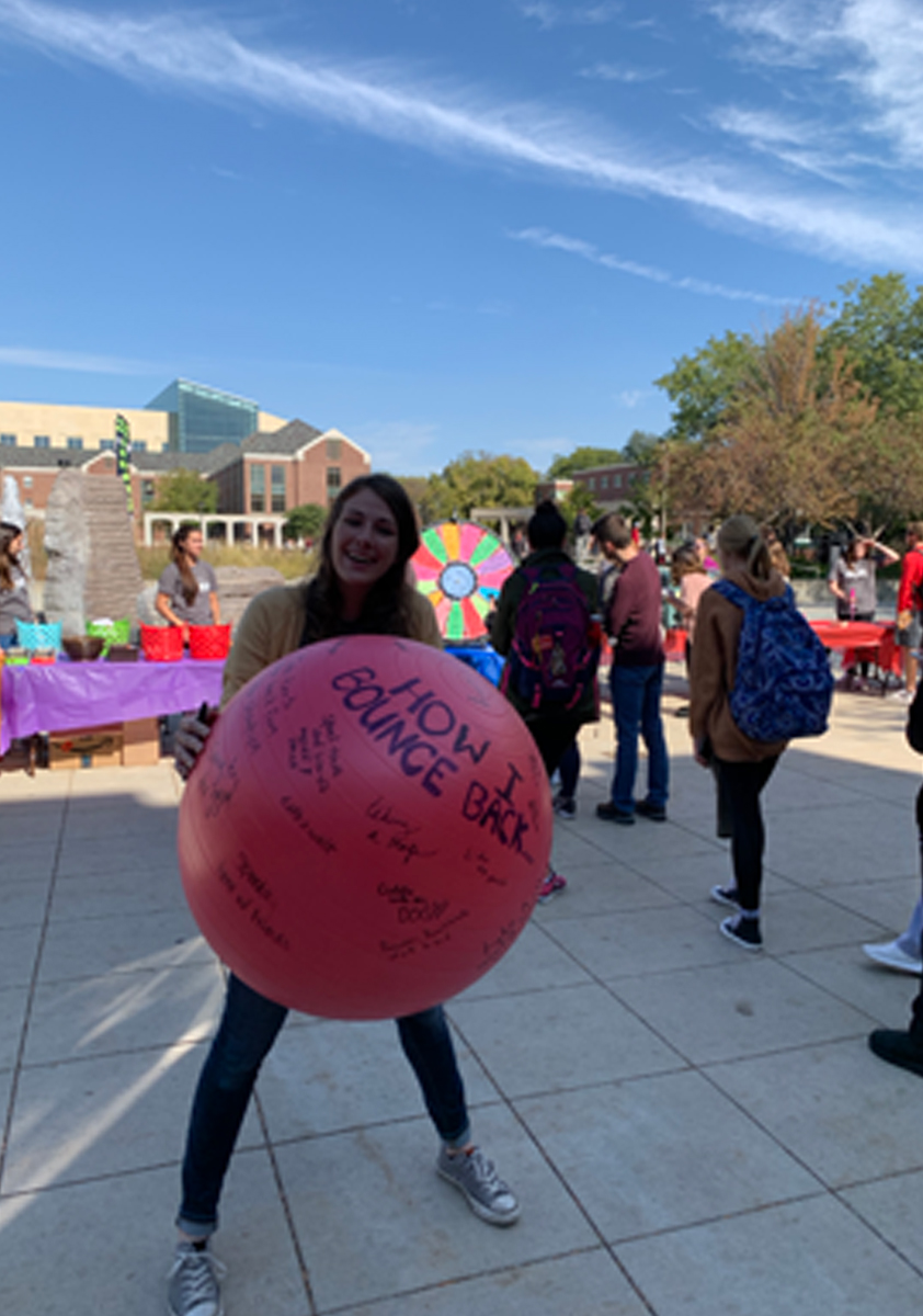 Woman catching a ball covered with written phrases at recess