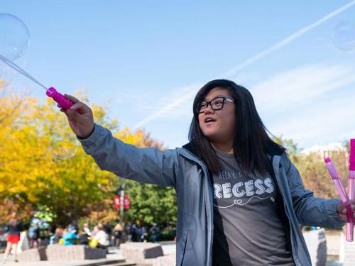 Woman making bubbles at recess